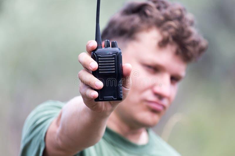 Un uomo con un walkie-talkie all'aperto fotografia stock