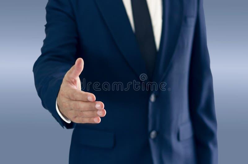 Un uomo d'affari è stante e stringente le mani fotografia stock