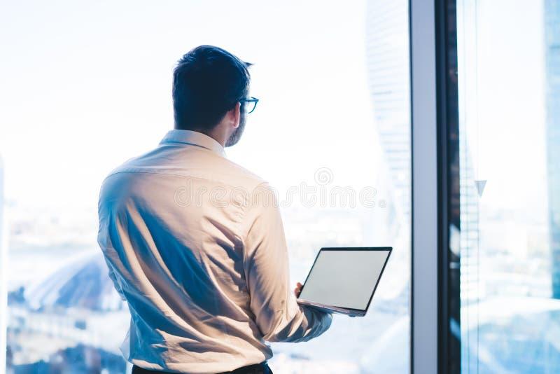 Un uomo d'affari attento a tenere il computer portatile in vetrina fotografie stock