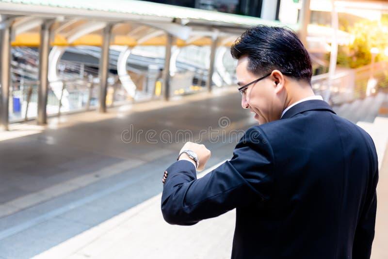 Un uomo d'affari bello sta guardando l'orologio per il controllo del tempo fotografie stock libere da diritti