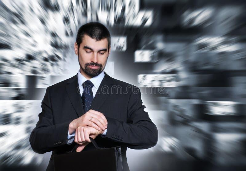 Un uomo d'affari bello in vestiti convenzionali che controlla il tempo fotografia stock libera da diritti