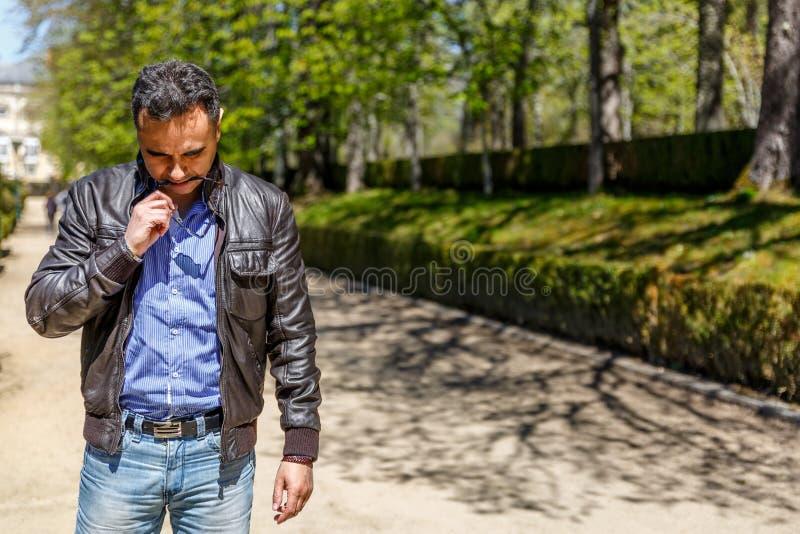 Un uomo d'affari in un bomber ed in una camicia blu, pensa a qualcosa mentre in mezzo ad un parco fotografia stock libera da diritti