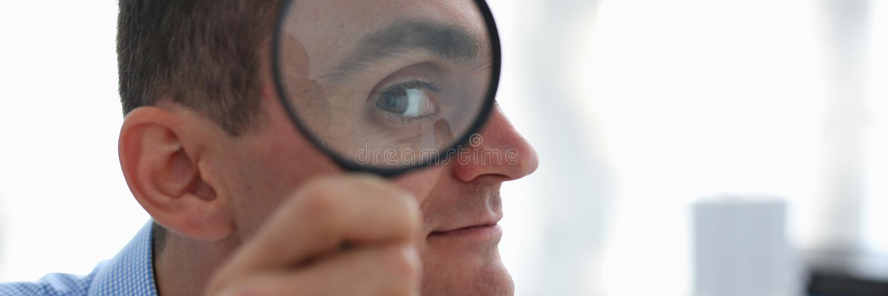 Un uomo d'affari in camicia blu sta tenendo un ingrandimento fotografia stock