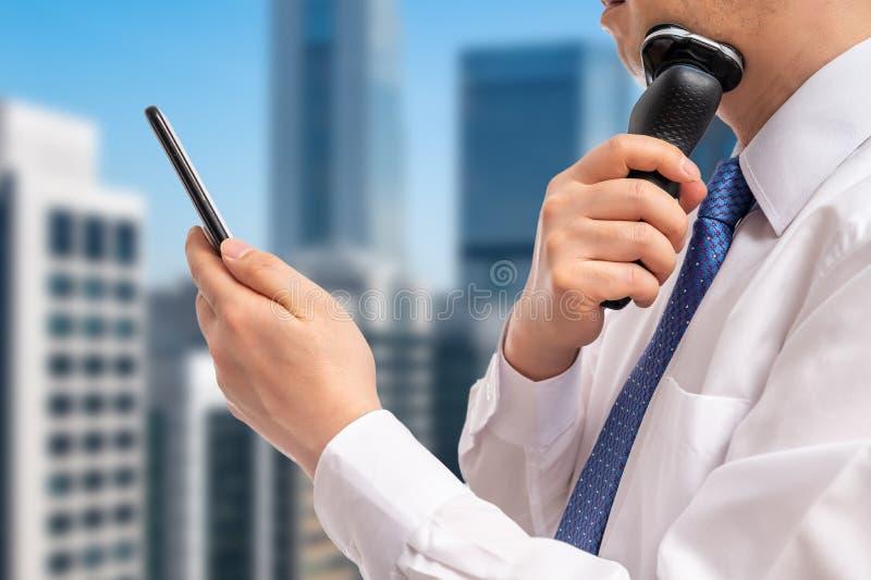Un uomo d'affari che guarda uno smartphone mentre si rasa Ora di punta mattutina fotografia stock
