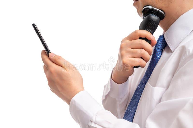 Un uomo d'affari che guarda uno smartphone mentre si rasa Ora di punta mattutina immagini stock