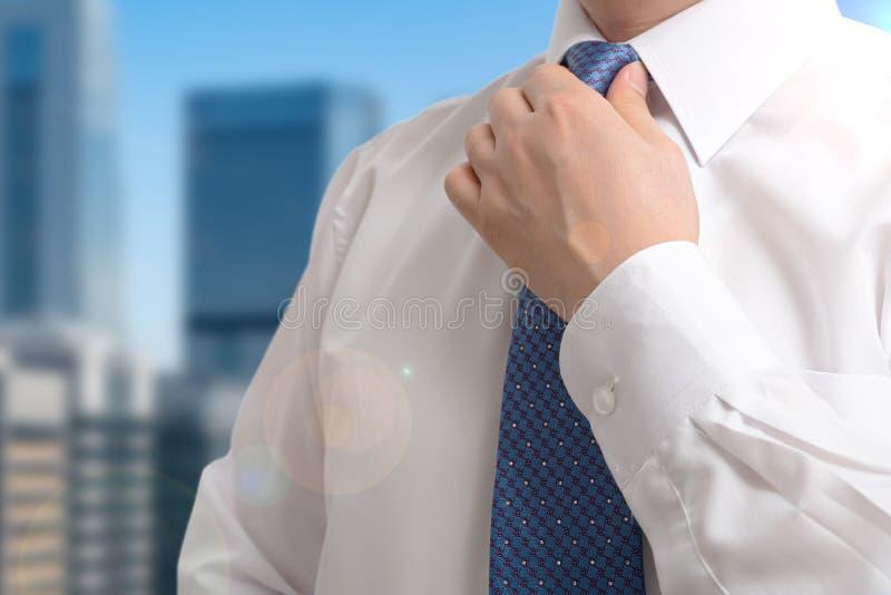Un uomo d'affari che indossa una cravatta e si prepara al lavoro la mattina fotografia stock