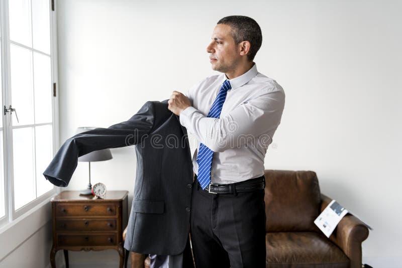 Un uomo d'affari che si agghinda per andare lavorare fotografia stock