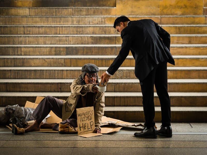Un uomo d'affari dà lo smartphone ad un uomo senza tetto che si siede su una scala fotografie stock libere da diritti