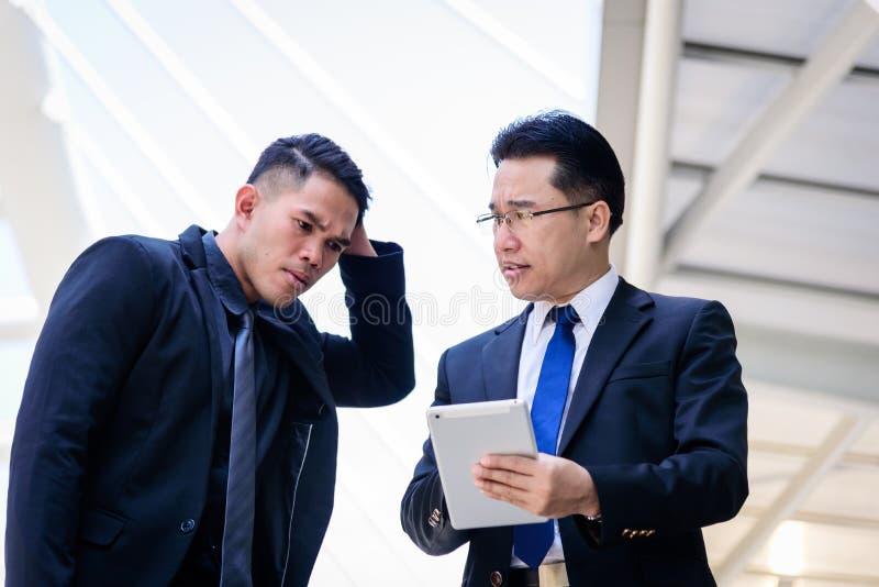Un uomo d'affari di due asiatici ha conversazione per la visione di affari fotografia stock libera da diritti