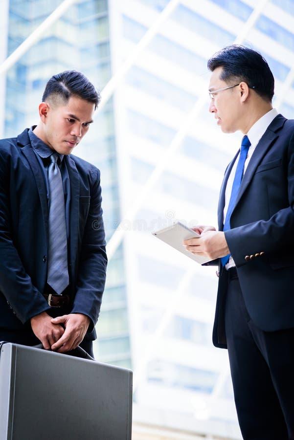 Un uomo d'affari di due asiatici ha conversazione per la visione di affari immagini stock libere da diritti