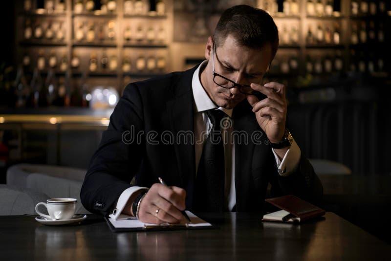 Un uomo d'affari elegante, serio e concentrato che si siede nel ristorante moderno e che fa le note in suo taccuino immagini stock libere da diritti