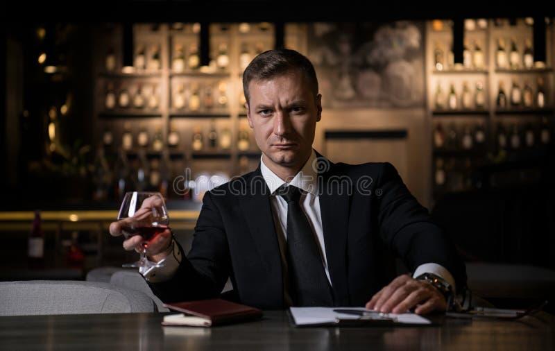 Un uomo d'affari elegante, serio e concentrato che tiene un vetro del cognac e che esamina macchina fotografica immagini stock
