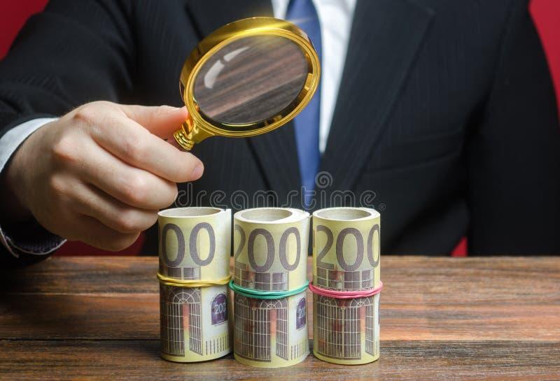 Un uomo d'affari ispeziona un fascio di monete in euro attraverso una lente di ingrandimento Investimenti in ricerca, progetti fi fotografia stock libera da diritti