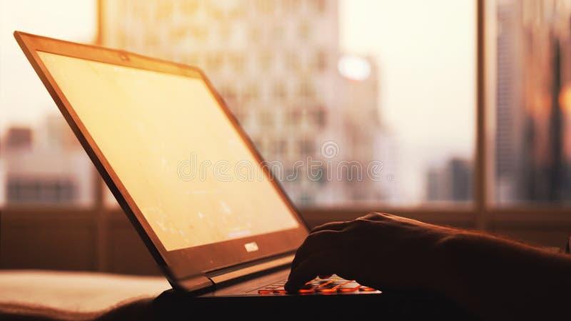 Un uomo d'affari lavora ad un computer portatile dalla grande finestra nelle costruzioni della città durante il tramonto Fine in  fotografie stock