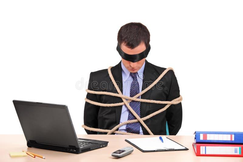 Un uomo d'affari legato in su con la corda nel suo ufficio fotografia stock libera da diritti