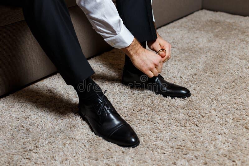 Un uomo d'affari in pantaloni del nero scuro e camicia bianca che legano i suoi laccetti delle scarpe Moderno, alla moda e costos fotografia stock libera da diritti