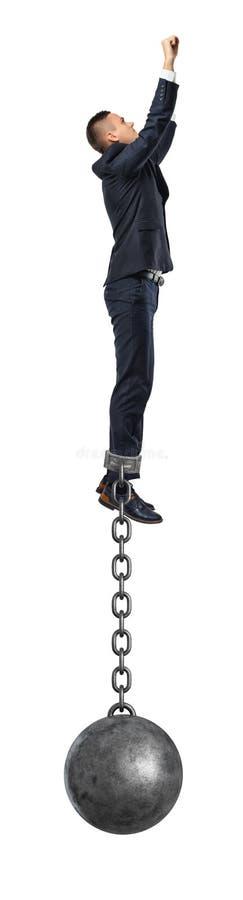Un uomo d'affari prende un supereroe salta nell'aria con una palla del ferro ancora allegata alla sua caviglia con una catena sol fotografia stock