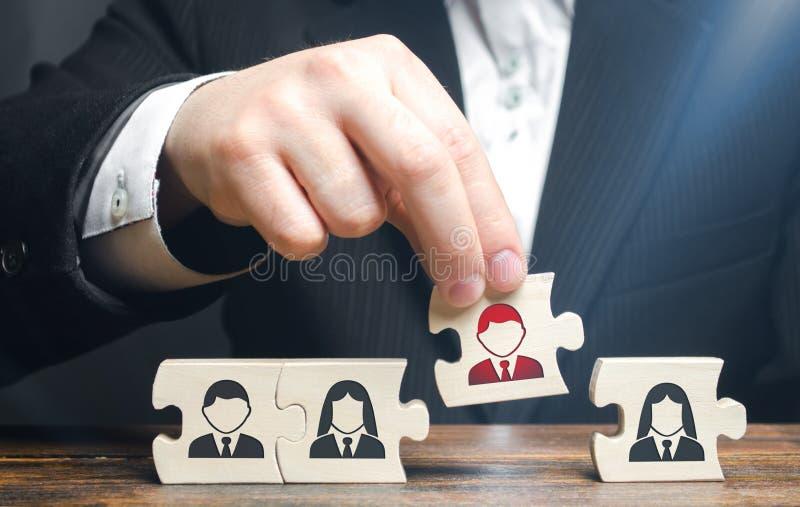 Un uomo d'affari raccoglie i puzzle che simbolizzano un gruppo degli impiegati Il concetto di creare un gruppo di affari per eseg fotografia stock libera da diritti
