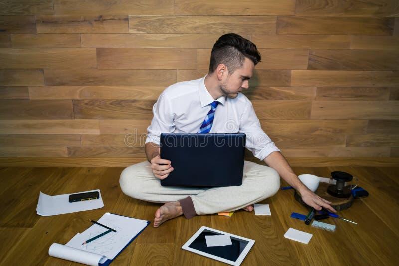 Un uomo d'affari scalzo che si siede sul pavimento contro una parete e che per mezzo del computer portatile immagine stock
