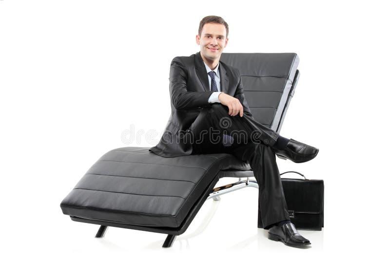 Un uomo d'affari situato su un sofà fotografia stock