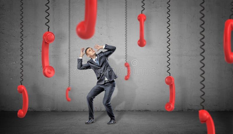 Un uomo d'affari spaventato su fondo concreto si nasconde da molti retro ricevitori rossi del telefono che appendono giù sui loro immagini stock