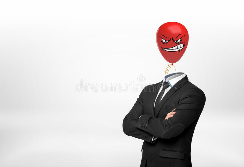 Un uomo d'affari su fondo bianco sta con le mani attraversate e un pallone arrabbiato rosso del fronte invece della sua testa fotografie stock