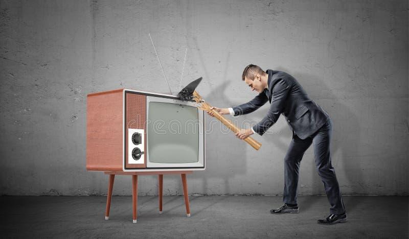 Un uomo d'affari su fondo concreto non riesce a fracassare un vecchio retro set televisivo con un martello rotto fotografia stock