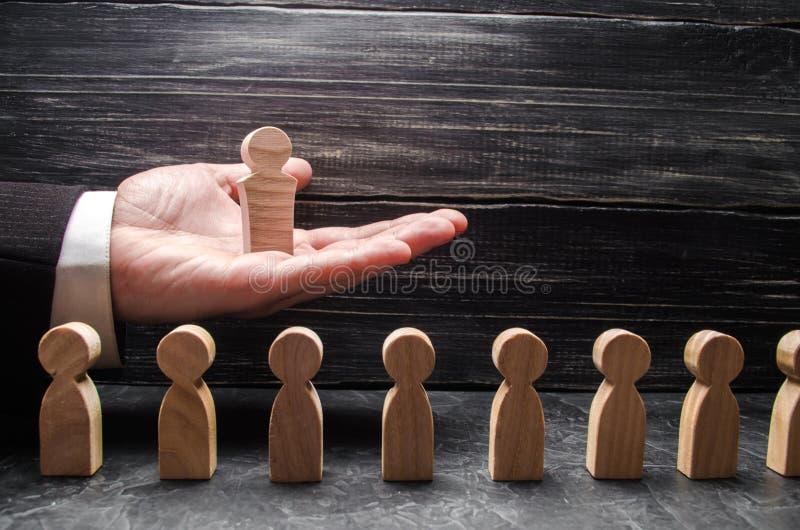 Un uomo d'affari tiene un capo di legno dipende la palma della sua mano sopra una serie di altri lavoratori Capo di concetto, lav fotografie stock