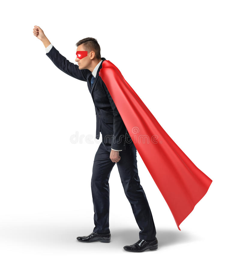 Un uomo d'affari in un capo rosso dell'eroe ed in una maschera di occhio che stanno nella vista laterale e che tengono un'insegna fotografia stock libera da diritti