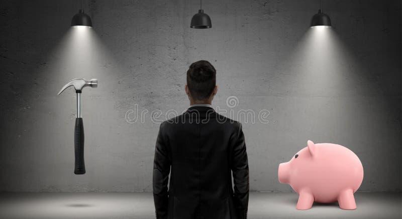 Un uomo d'affari in una vista posteriore guarda fra un martello e un porcellino salvadanaio che stanno sotto le lampade industria fotografie stock libere da diritti