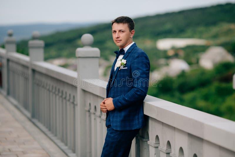Un uomo d'affari in un vestito blu alla moda sta stando su un balcone di pietra contro un contesto delle colline verdi Un uomo al fotografia stock libera da diritti