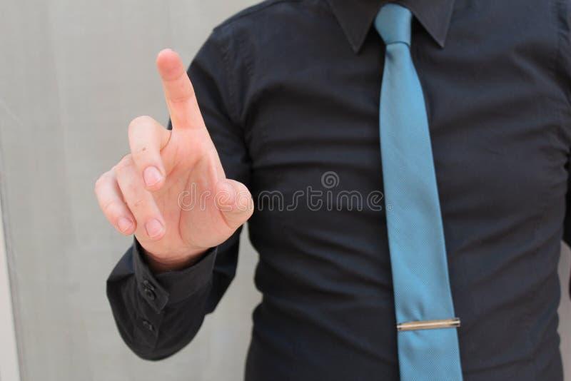 Un uomo d'affari in un vestito ed in un legame che indica con il dito, per l'implementazione di futuristico grafico Concetto: aff fotografia stock libera da diritti