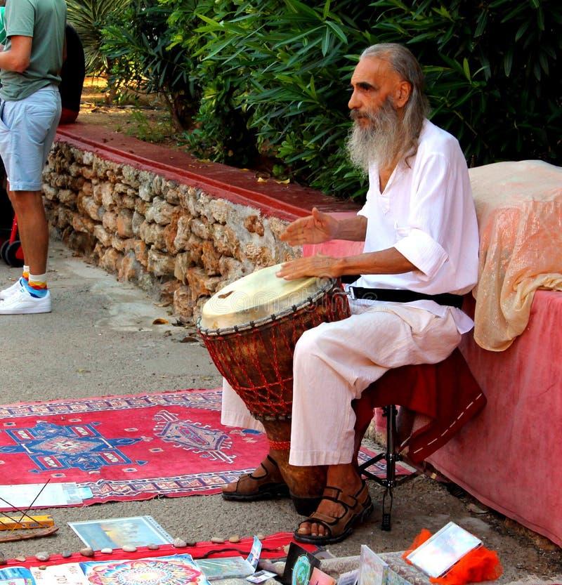 Un uomo del musicista dell'artista della via sta giocando con le sue mani uno strumento di percussione come un tamburo immagine stock libera da diritti