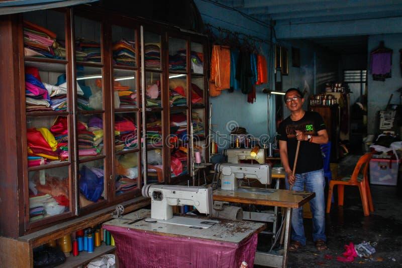 Un uomo della cucitrice pulisce nel suo padiglione con le macchine per cucire ed in una grande selezione dei tessuti immagini stock