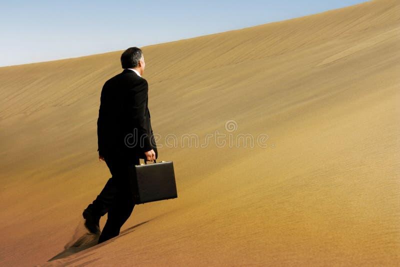 Un uomo di affari che funziona attraverso il fronte di una duna immagini stock libere da diritti