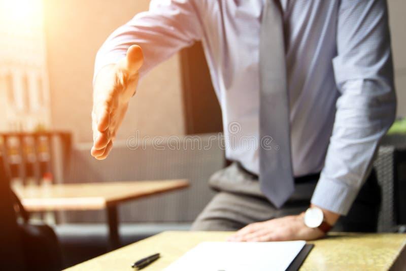 Un uomo di affari con una mano aperta ha estendere alla stretta di mano immagine stock libera da diritti