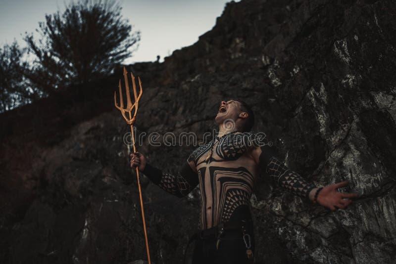 Un uomo di furia con un tridente in sue mani contro lo sfondo delle rocce fotografia stock