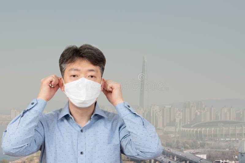 Un uomo di mezza età che indossa una maschera nei precedenti di una città in pieno di polvere fine immagini stock