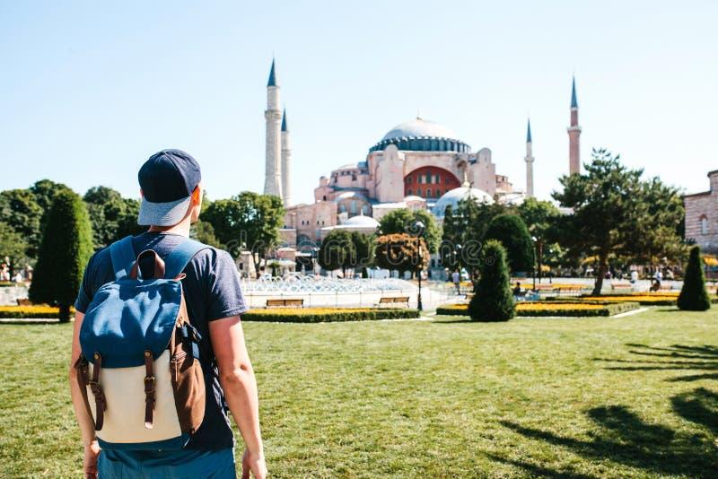Un uomo di viaggio con uno zaino nel quadrato di Sultanahmet vicino alla moschea famosa di Aya Sofia a Costantinopoli in Turchia immagini stock