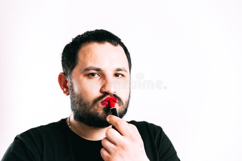 Un uomo dipinge le sue labbra con rossetto fotografie stock