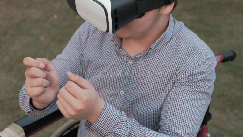 Un uomo disabile in una sedia della sedia a rotelle usa un casco di realtà virtuale fotografia stock