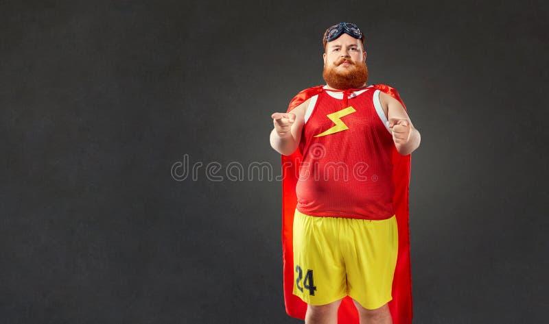 Un uomo divertente grasso in un costume del supereroe indica una mano voi fotografie stock