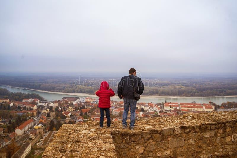 Un uomo e un bambino guardano dall'alto in basso la città, stante sulla cima della collina ed esamina giù la valle immagini stock libere da diritti