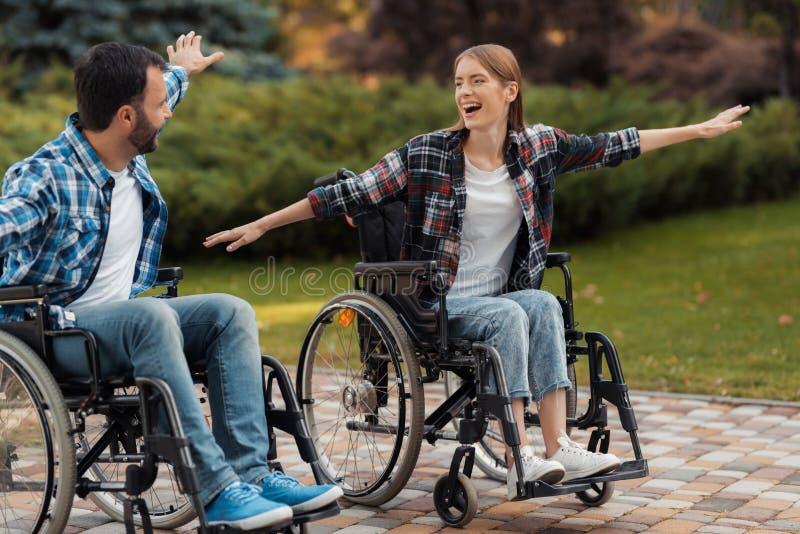 Un uomo e una donna sulle sedie a rotelle guidano intorno al parco Hanno accantonato le loro mani ed hanno imbrogliato intorno fotografia stock libera da diritti
