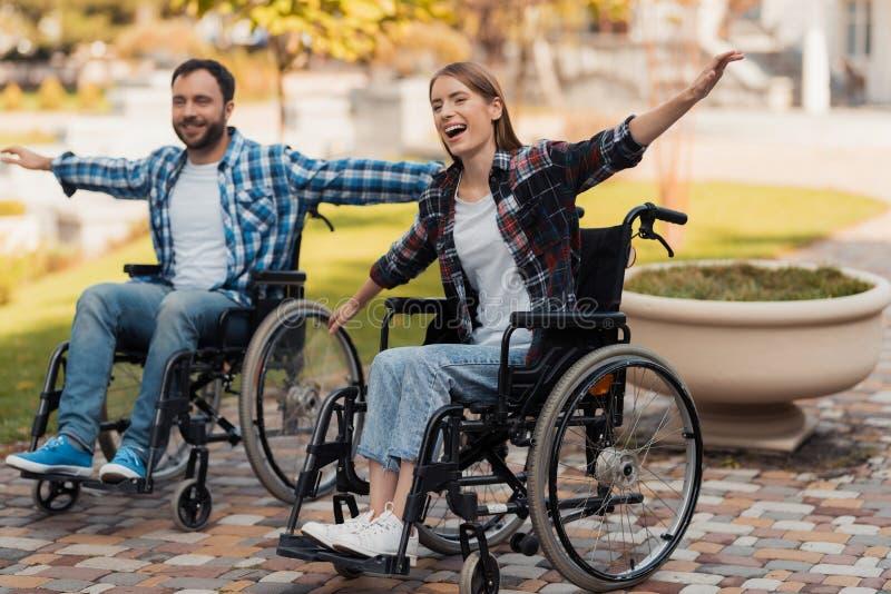 Un uomo e una donna sulle sedie a rotelle guidano intorno al parco Hanno accantonato le loro mani ed hanno imbrogliato intorno fotografie stock