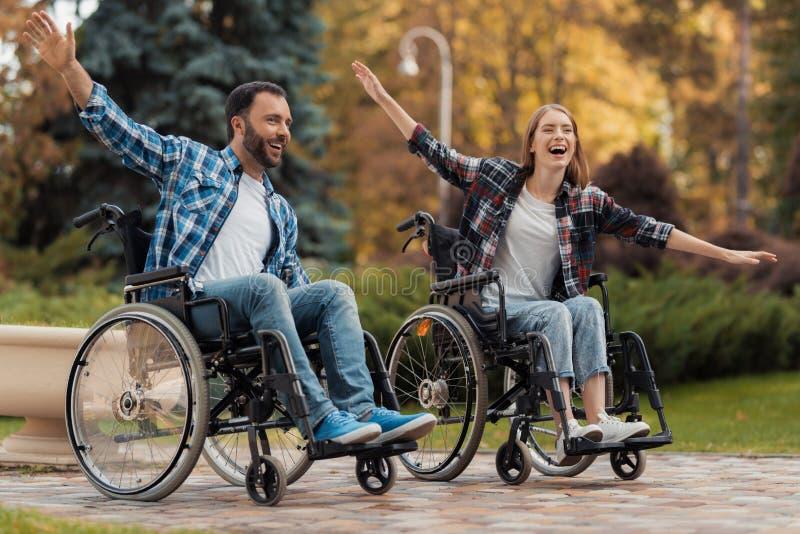 Un uomo e una donna sulle sedie a rotelle guidano intorno al parco Hanno accantonato le loro mani ed hanno imbrogliato intorno immagine stock