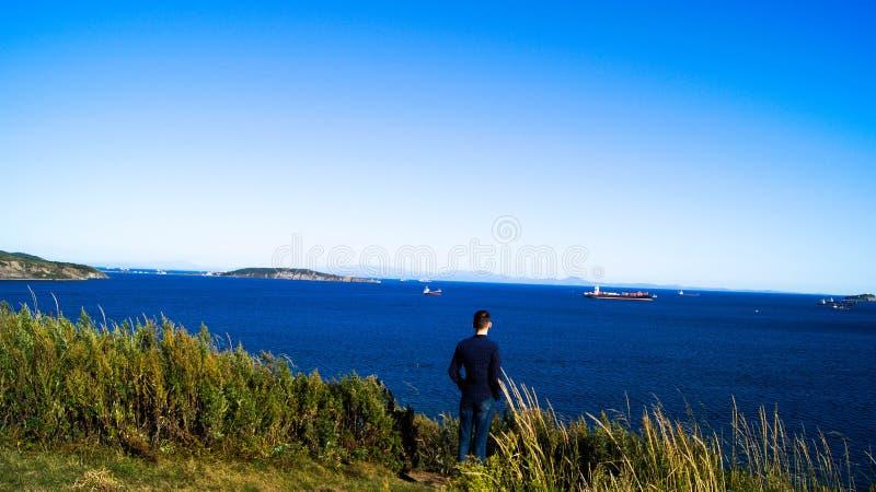 Un uomo esamina le navi sulla spiaggia immagini stock