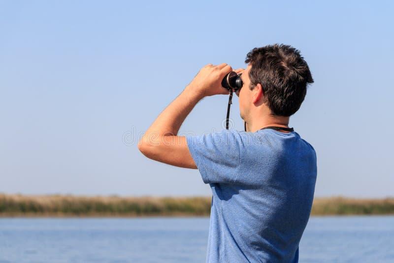 Un uomo esamina tramite il binocolo il fiume fotografia stock libera da diritti