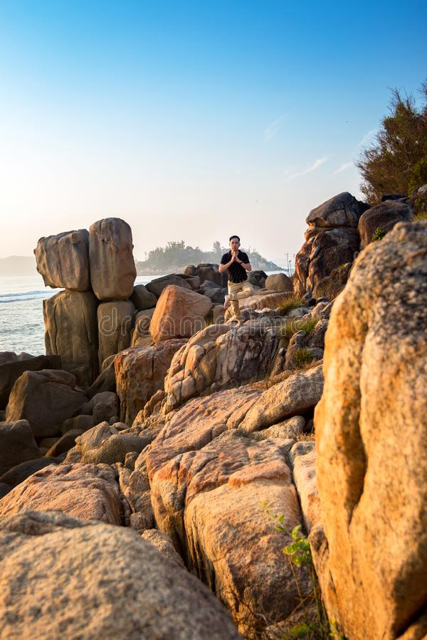 Un uomo fa l'yoga sul sole dei massi di mattina immagini stock