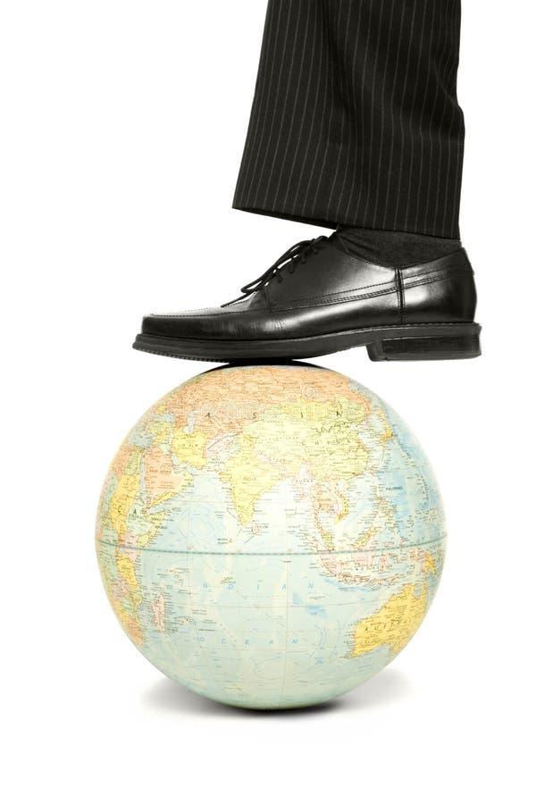Un uomo fa un passo su un globo immagine stock libera da diritti